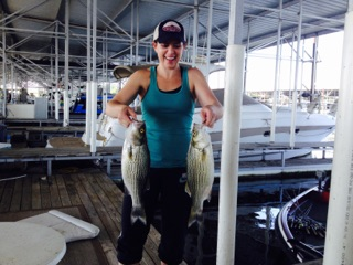 Lady with two trophy Hybrid Bass caught on a guided fishing trip