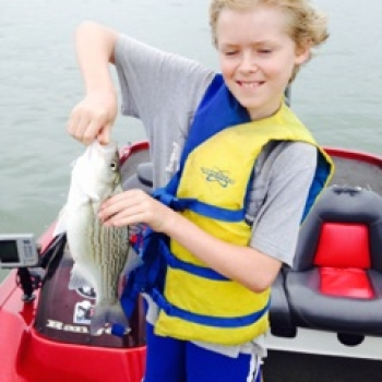 Kid with a Hybrid Bass caught on a Lake Lewisville guided fishing trip